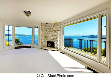 Luxury real estate bedroom with water view and fireplace. - ...