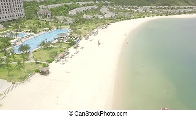 Luxury resort hotels on tropical sea beach with swimming pool drone view. Aerial landscape tourist resort hotel with swimming pool and on blue sea shore.
