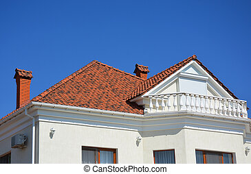 Luxury roofing constraction with natural clay roof tiles, house attic balcony and metal shutters, blinds.