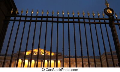 Luxury royal palace behind a high solid fence at night, view...