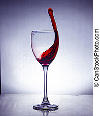 luxury splash drink in a glass on a high leg on a colored background