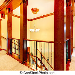 Luxury staircase with wood columns and metal railings and yellow walls.