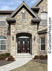 Luxury stone home with stain glass windows on door