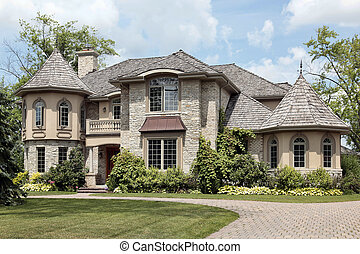 Luxury stone home with turret and cedar shake roof