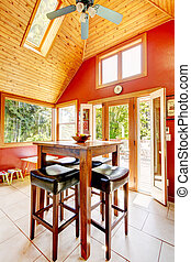 Luxury vaulted wood ceiling dining room with red walls.