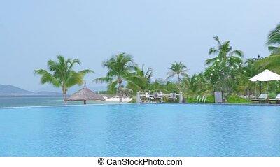 Luxury villa hotel resort and blue swimming pool on sea beach and modern city panorama. Luxury infinity pool and resort hotel on sea shore with panoramic view on modern city.