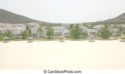 Luxury villas and mansion in resort hotel with swimming pool on tropical island at sea shore. Aerial view from flying drone cottage village in on sea shore.