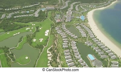 Luxury villas and resort hotels on tropical island and blue sea landscape view from flying drone. Aerial landscape luxury cottage village with houses, swimming pool and golf course on blue sea shore.