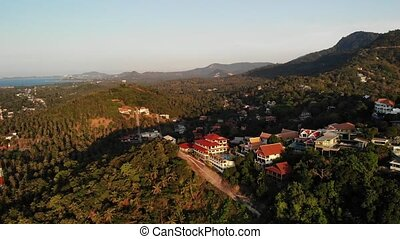 Luxury villas on mountain slope. Drone view of houses located amidst exotic trees on green mountains on sunny day on tropical island.
