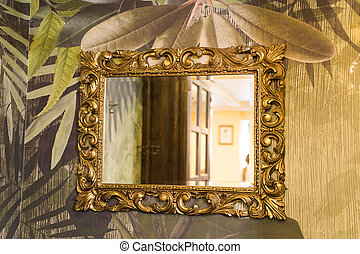 Luxury vintage mirror with gold frame on the wall. Isolated inside