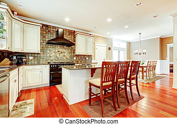 Luxury white kitchen with cherry hardwood and island with chairs.