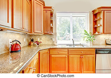 Luxury Wood kitchen with granite and window.
