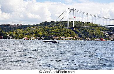 Luxury yacht / boat crosses Bosphorus between European and Asian sides in Istanbul. FSM (Fatih Sultan Mehmet) bridge is in the background. It is significant waterway located in northwestern Turkey