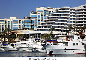 Luxury Yachts Docked In Front Of Waterfront Hotels