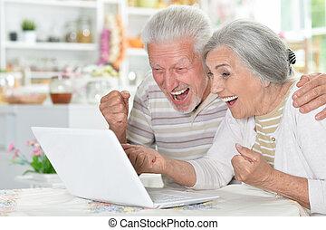 lycklig, äldre koppla, användande laptop