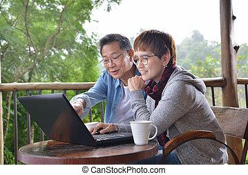 lycklig, äldre koppla, användande laptop, dator