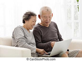 lycklig, äldre koppla, användande laptop, på, soffa