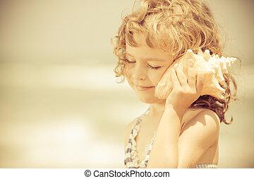 lycklig, barn, lyssna till, snäckskal, stranden