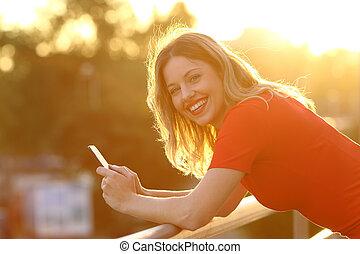 lycklig, flicka, tittande vid, dig, med, a, smart, ringa, hos, solnedgång
