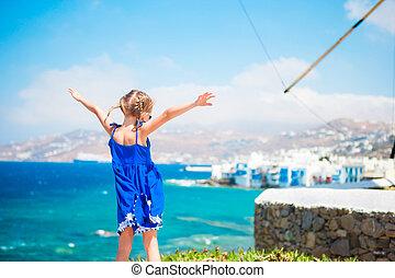 lycklig, liten flicka, med, synhåll, på, litet venedig, den, mest, populär, turist, område, på, mykonos ö, greece.