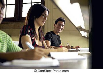 lycklig, student, studera, och, skrift, stående, av, hispanic, ung man, gör, hemarbete, in, högskola, bibliotek, och, le, kamera