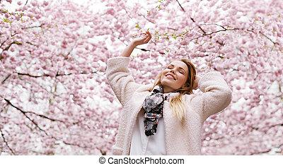 lycklig, ung kvinna, avnjut, nytt lufta, hos, fjäder, blomma, parkera