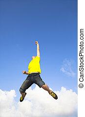lycklig, ung man, hoppning, med, moln, bakgrund