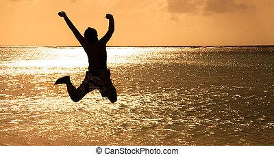 lycklig, ung man, hoppning, stranden, hos, solnedgång