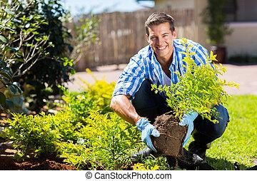 lycklig, ung man, trädgårdsarbete