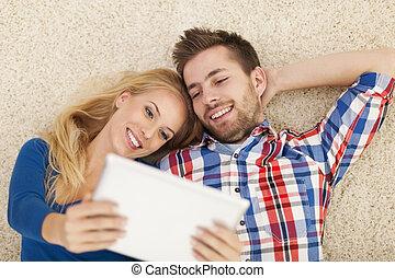 lycklig, ungt par, med, samtidig, digital tablet, på, matta