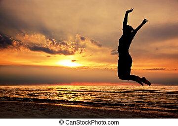 lycklig woman, hoppning, stranden, hos, solnedgång