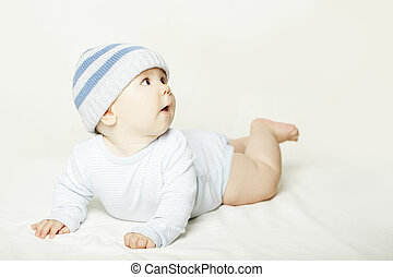 Lying baby on gray background