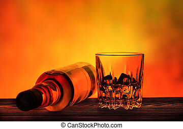 Lying bottle and a glass of whiskey with ice