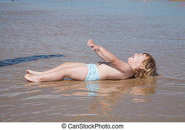 lying laughing baby at seaside