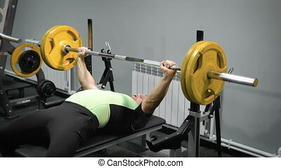 Lying man do exercise with barbell