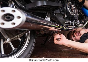 Lying Man Fixing his Motorbike Using Wrench Tool
