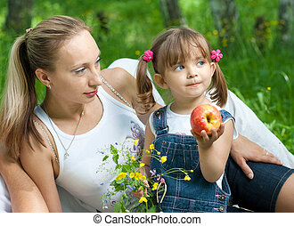 Lying mother and daughter in jeans with apple outdoor