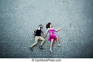 Lying on pavement - Image of affectionate dates lying on...