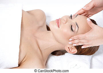 Lying on spa bed - Young pretty woman getting head massage