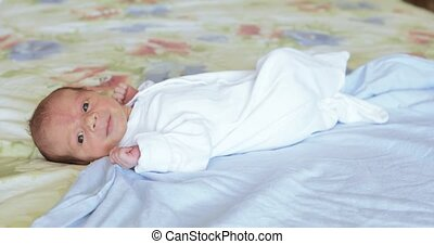 Lying on the bed sheet baby - A breastfed baby wrapped in a...