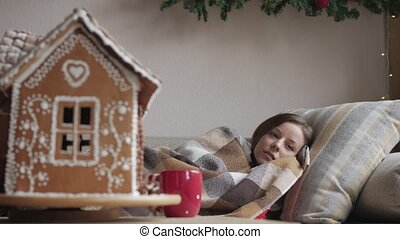 lying on the sofa under a blanket. health and illness concept - of diseased woman with cup of tea. Christmas morning.