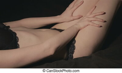 Lying sexual woman touching her body on black background