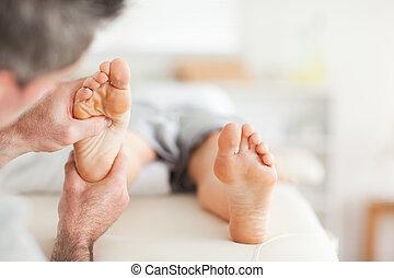 Lying Woman getting a reflexology massage