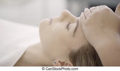 Lying woman hands make facial massage with light movements.