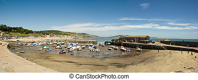 Lyme Regis harbor at low tide with boats high and dry