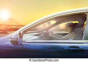 más joven, mujer, conducción, automóvil, en, urbano, contra, cielo de puesta de sol, ciudad