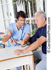 mâle, infirmière, vérification, tension artérielle, de, a, personne agee, patient