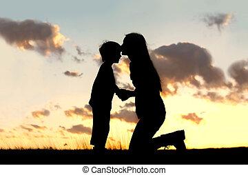 mãe, amorosamente, beijando, criança pequena, em, pôr do sol