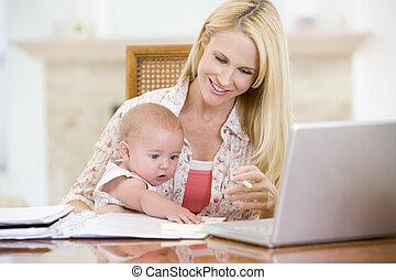 mãe bebê, em, jantando quarto, com, laptop, sorrindo