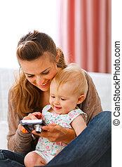 mãe, câmera, bebê, jovem, mostrando, sorrindo, fotografias, dela